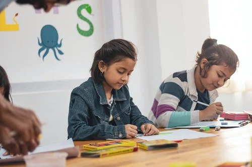 kids learning how to draw on their classroom table